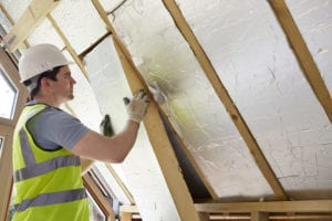 photo of man installing panels of insulation in attic