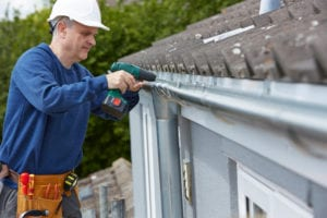 photo of man installing new gutters on home