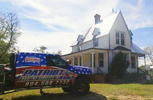 photo of Patriot Roofing truck in front of house